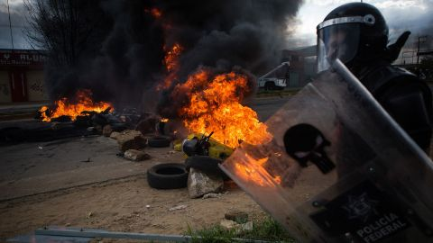 """An officer walks past burning debris during <a href=""""http://www.cnn.com/2016/06/20/americas/oaxaca-mexico-clashes/index.html"""">deadly clashes between striking teachers and police</a> in Oaxaca, Mexico, on Sunday, June 19. The violence came after seven days of protests disrupting traffic on a major highway connecting Oaxaca to Mexico City, the government said."""