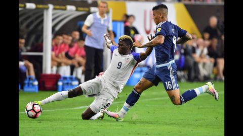 Gyasi Zardes slides to win possession for the United States.