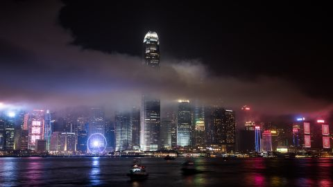 The IFC tower is seen shrouded in smoke after fireworks were fired over the city skyline as part of China's national day celebrations in Hong Kong on October 1, 2015. China is marking the 66th anniversary of the founding of the People's Republic of China on October 1, 1949.  AFP PHOTO / Philippe Lopez        (Photo credit should read PHILIPPE LOPEZ/AFP/Getty Images)