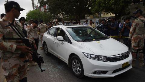 Pakistani security officials inspect the bullet-riddled car of Sufi musician Amjad Sabri.