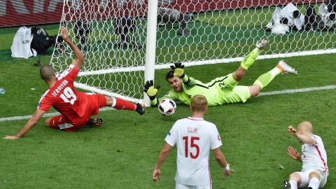 Poland goalkeeper Lukasz Fabianski, top right, saves an attempt by Switzerland forward Eren Derdiyok, left.