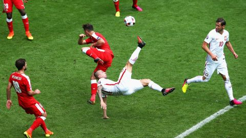 Kamil Grosicki of Poland attempts an overhead kick while Granit Xhaka of Switzerland tries to block.