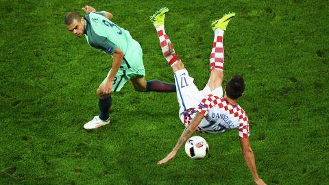 Mario Mandzukic of Croatia falls heavily while competing with Pepe of Portugal.