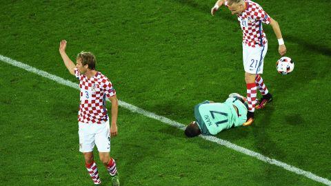 Ivan Strinic, left, and Domagoj Vida, right, of Croatia protest as Portugal forward Nani falls in the penalty area.