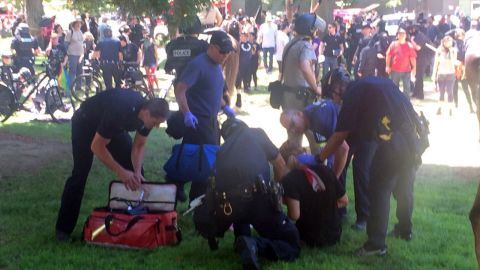 A man injured during the rally is assisted by police and emergency personnel.