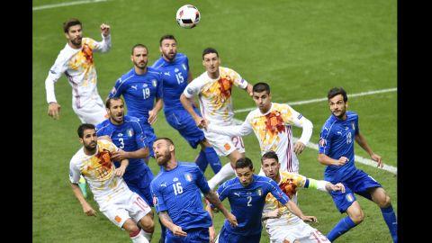 Italian midfielder Daniele De Rossi (No. 16)heads the ball in the box.