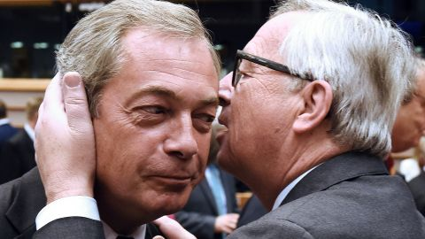European  Commission President Jean-Claude Juncker speaks in the ear of UK Independence Party leader Nigel Farage Tuesday.
