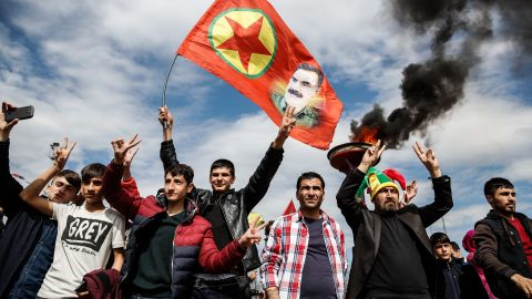 DIYARBAKIR, TURKEY - MARCH 21: Kurdish men flash v-signs as they  hold up a flag with a picture of the jailed PKK leader Abdullah Ocalan during Newroz celebrations, on March 21, 2015 in Diyarbakir, Turkey. Thousands of Kurds gather for the Newroz spring festival in Diyarbakir in southeast Turkey under tight security after months of fighting between security forces and Kurdish separatists, and a series of bombings in Istanbul and Ankara. (Photo by Ulas Tosun/Getty Images)