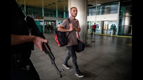 A police officer stands guard as a man walks at the airport a day after the attack.