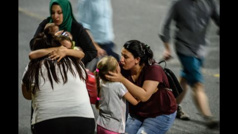 Children and their relatives embrace after reuniting outside the airport.