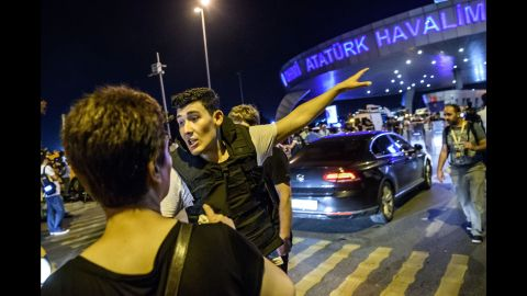 A Turkish police officer directs a passenger at the airport.