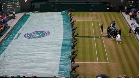 Play suspended! Ground staff rush to cover a Wimbledon show court as rain halts proceedings.