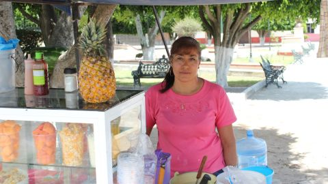 Elizabeth Villafuerte, 42, has had a fruit stand for 21 years. She says money transfers help the town, but even that isn't enough.