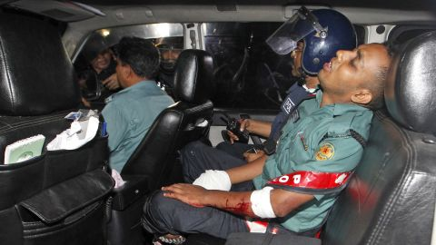 An injured police officer sits in a car. The attackers threw explosives at police as they exchanged gunfire, a source at the scene said.