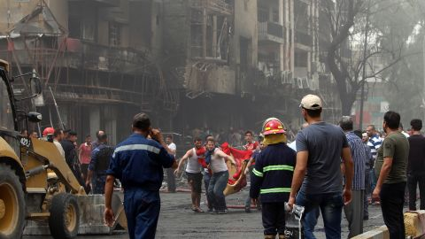 Iraqis on Sunday evacuate a body from the site of a suicide car bombing in Baghdad's central Karrada district.