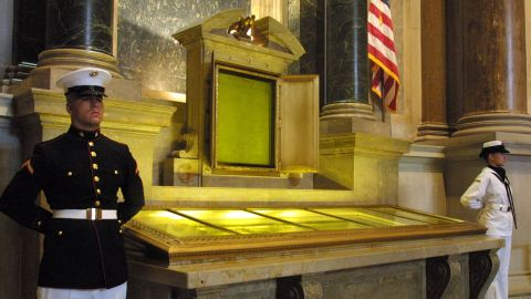An honor guard stands next to the original copies of the Declaration of Independence, the Constitution and the Bill of Rights July 4, 2001 at the National Archives in Washington, D. C.
