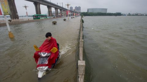 A man rides a scooter across a flooded bridge in Wuhan, July 2.<br />