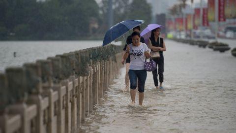 People cross a flooded bridge in Wuhan on July 2.