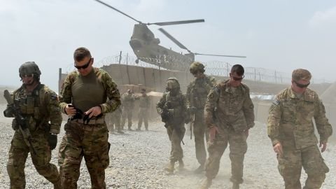 """In this photograph taken on August 13, 2015, US army soldiers walk as a NATO helicopter flies overhead at coalition force Forward Operating Base (FOB) Connelly in the Khogyani district in the eastern province of Nangarhar. From his watchtower in insurgency-wracked eastern Afghanistan, US army Specialist Josh Whitten doesn't have much to say about his Afghan colleagues. """"They don't come up here anymore, because they used to mess around with our stuff. """"Welcome to Forward Operating Base Connelly, where US troops are providing training and tactical advice to the 201st Afghan army corps as they take on the Taliban on the battlefield."""