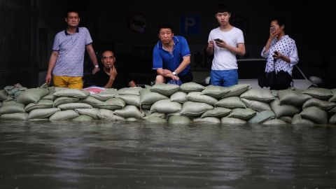 Residents stand behind sandbags on a flooded street in Wuhan, Hubei province, July 6. More than 10 million people in the province have been affected -- a sixth of the population.