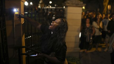 A woman rings the doorbell at the gate of the governor's mansion in St. Paul, Minnesota.