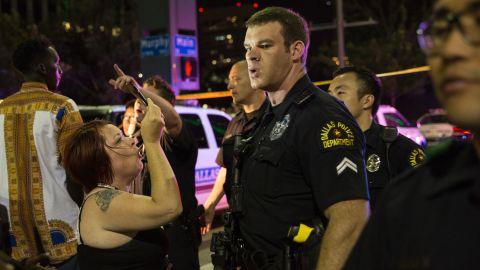 Police attempt to calm the crowd as someone is arrested following the sniper shooting in Dallas on July 7, 2016.  A fourth police officer was killed and two suspected snipers were in custody after a protest late Thursday against police brutality in Dallas, authorities said. One suspect had turned himself in and another who was in a shootout with SWAT officers was also in custody, the Dallas Police Department tweeted.  / AFP / Laura Buckman        (Photo credit should read LAURA BUCKMAN/AFP/Getty Images)