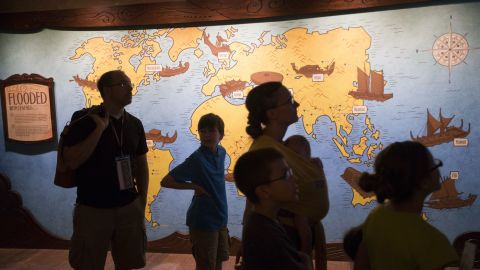 Visitors pass through an exhibit displaying various flood legends.