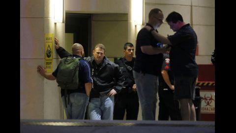 Law enforcement officials wait outside the emergency room entrance at Baylor University Medical Center.