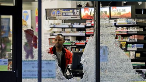 A clerk looks at broken windows that were shot out at a store in downtown Dallas.