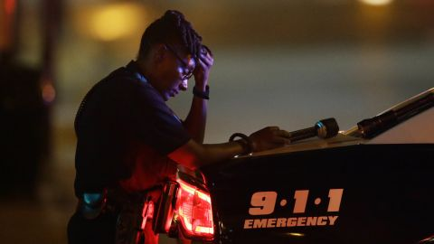 A Dallas police officer, who did not want to be identified, takes a moment as she guards an intersection in the early morning after a shooting in downtown Dallas, Friday, July 8, 2016. At least two snipers opened fire on police officers during protests in Dallas on Thursday night; some of the officers were killed, police said.
