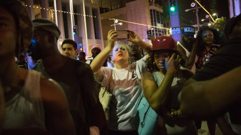 Protesters gather as police officers arrest someone in the aftermath of the shootings.