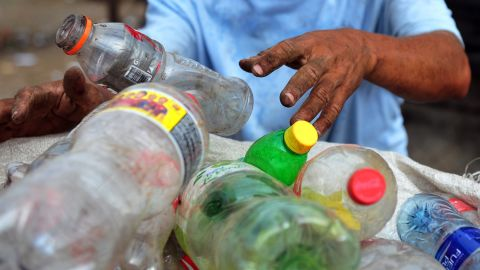 A man collects plastic bottles to sell for recycling, in a landfill of Managua, on January 11, 2013.  AFP PHOTO/Hector RETAMAL        (Photo credit should read HECTOR RETAMAL/AFP/Getty Images)