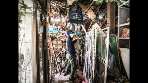 Loong, wearing a mask, looks through abandoned houses. Loong appears in most of his photos. He sets his camera on a tripod and a timer and shoots.