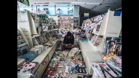Loong sits in an abandoned store with books and magazines sprawled around him.