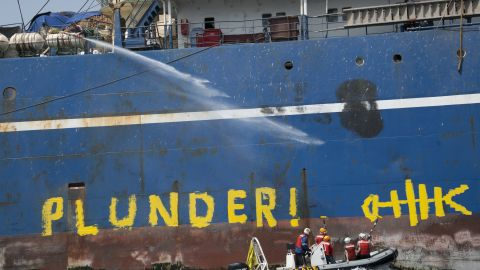 """Activists from the Greenpeace ship Arctic Sunrise paint """"Pillage and Plunder"""" on side of pirate Russian pelagic fishing trawler Oleg Naydenov off the coast of Senegal."""