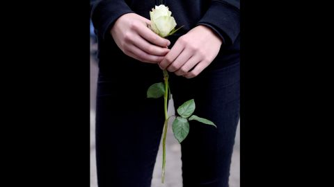 Apupil holds a white rose on the premises of the Paula Fuerst comprehensive school in Berlin,Germany.