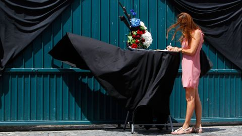 A woman signs a condolence book in front of the French Embassy in Bucharest, Romania.