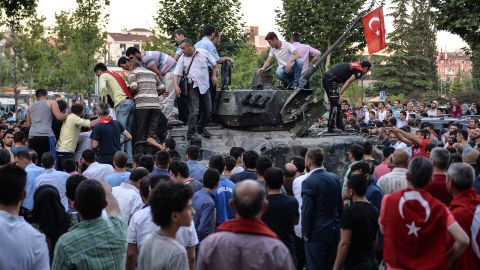 People gather on top of a Turkish military tank in Ankara in the morning after the coup attempt. National intelligence officials said the coup was put down and that the government remains in control.