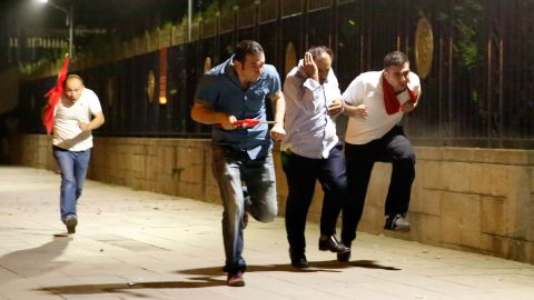 People escape the clashes in Ankara early Saturday.