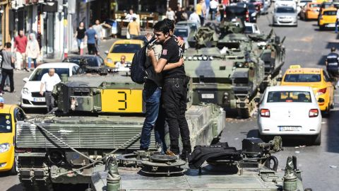 A Turkish police officer in Istanbul embraces a man on a tank in the wake of the violence overnight.