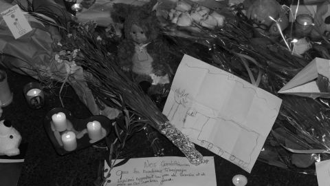 People left candles and messages at a memorial site. On one of the pieces of paper, a child drew a truck.