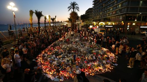 People gather at a makeshift memorial on the Promenade des Anglais in Nice on Sunday, July 17. ISIS has claimed responsibility for the truck rampage, but the French interior minister said that any link between the attacker -- Mohamed Lahouaiej-Bouhlel -- and the terror group has yet to be established.