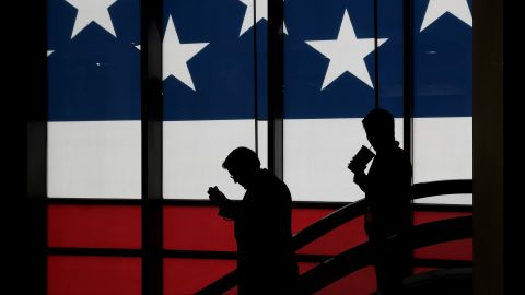 People walk in front of a screen displaying the American flag.