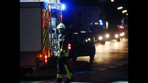 A rescuer stands on a road near the railroad tracks in Wurzburg.