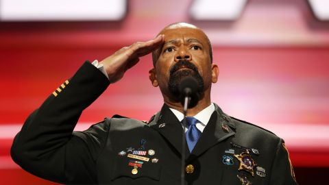 """Milwaukee County Sheriff David A. Clarke Jr. salutes the crowd before speaking Monday. He got huge applause when he started off his speech by saying, """"Blue lives matter!"""""""