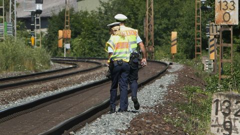 """Officers walk along train tracks in Wurzburg on July 19, a day after the attack. German authorities said they had found a hand-drawn flag resembling the one used by ISIS among the Afghan man's belongings. A pro-ISIS media group said the attacker was an """"ISIS fighter,"""" but authorities cast doubt on that claim."""