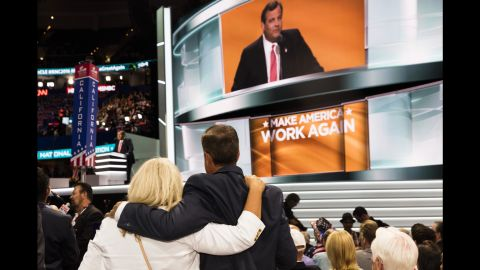 People watch New Jersey Gov. Chris Christie deliver a speech.