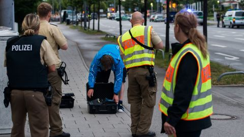 Police officers search a man outside the shopping mall where the shooting took place.