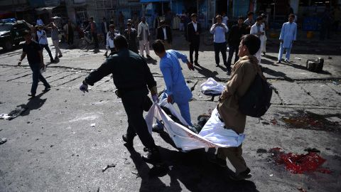 Afghan volunteers carry the bodies of victims at the scene of a suicide attack that targeted crowds of minority Shiite Hazaras during a demonstration at the Deh Mazang Circle of Kabul on Saturday, July 23.