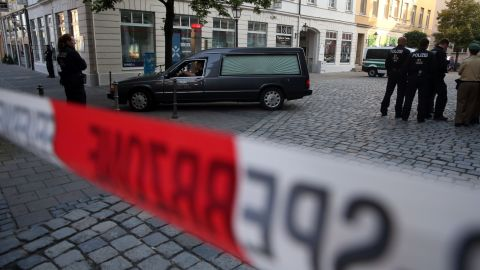 Police watch a hearse leave the scene of a suicide attack in the southern German city of Ansbach.